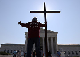 A demonstrator in Washington holds a large cross outside the U.S. Supreme Court  July 8, 2020.